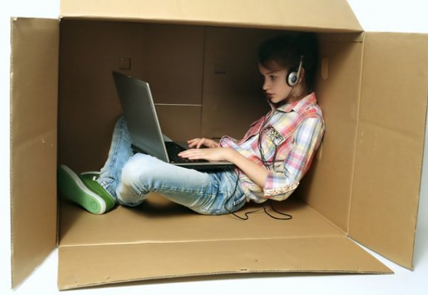 teen in box with laptop